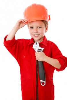 Little builder in helmet with wrench
